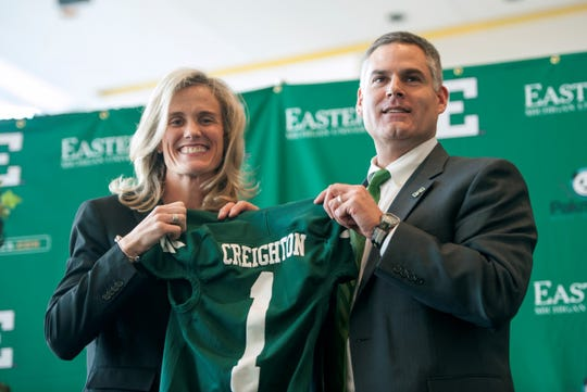Eastern Michigan University, vice president/director of Intercollegiate Athletics Heather Lyke, left, and new head football coach Chris Creighton hold up a football jersey together after Creighton was named the new coach in  December 2013.