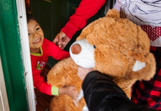 Four-year-old Liam Gonzalez of Southwest Detroit accepts the gift of a giant teddy bear from Jimmy's Kids, delivered by Jewish volunteers Adrienne Lenhoff and Jack Cohen on Christmas Day.