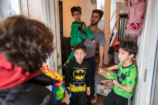 Alex Aviles, of Southwest Detroit, and his three sons Tony, 6, Noah, 7, and Aron, 8, get a surprise visit and free toys from Jimmy's Kids volunteer Adrienne Lenhoff on Christmas Day.