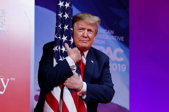 President Donald Trump hugs the American flag as he arrives to speak at the Conservative Political Action Conference, CPAC 2019, in Oxon Hill, Md., on March 2, 2019.