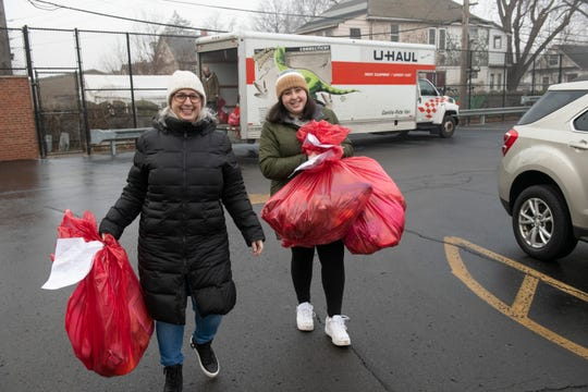 Volunteers Carolyn Fox, left, and her daughter Morgan Berg, both of Farmington Hills carry bags filled with Christmas toys from Jimmy's Kids to deliver to children in Southwest Detroit on Christmas Day.