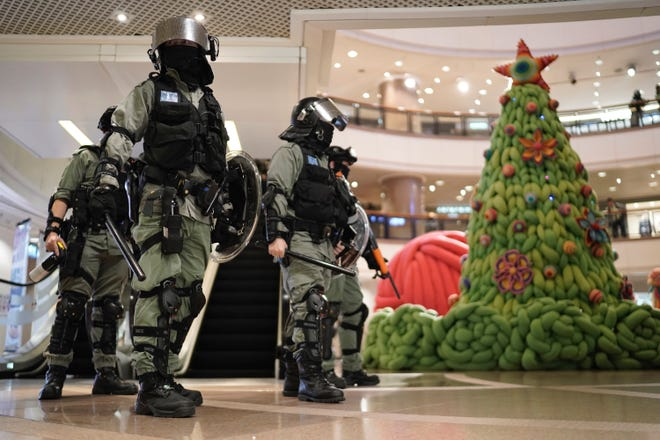 Riot police past by a Christmas decor in a mall during a protest rally on Christmas Eve in Hong Kong on Tuesday, Dec. 24, 2019.