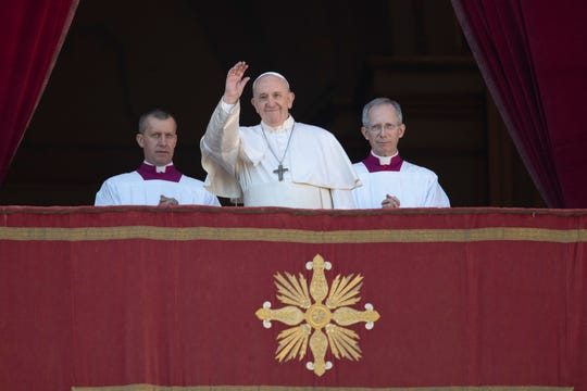Pope Francis waves to faithful and pilgrims after he delivered the Urbi et Orbi (Latin for 'to the city and to the world' ) Christmas' day blessing from the main balcony of St. Peter's Basilica at the Vatican on Wednesday.