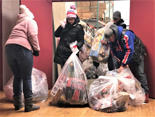 Volunteers leave Arctic League headquarters in Elmira on Christmas morning laden down with gift bags for needy families.