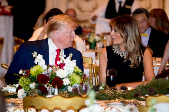 President Donald Trump and first lady Melania Trump talk at Mar-a-lago while there for Christmas Eve dinner in Palm Beach, Fla., Tuesday, Dec. 24, 2019.
