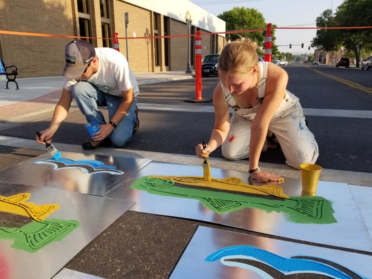 Abigail Lichliter and Clark Carlson-Thompson, Get Fit Great Falls volunteers, paint crosswalks downtown. The effort aims to make downtown more friendly and walkable.