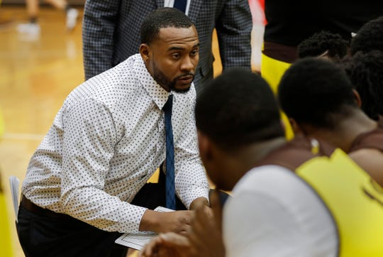 Head coach of Howe basketball team, Deandre Brock talks with players on the sidelines during a game at Thomas Carr Howe High School, Indianapolis, Thursday, Dec. 19, 2019.