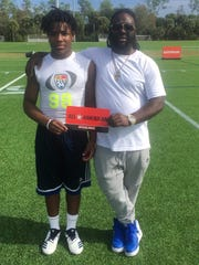 Miequle Brock Jr. (left) holds his FBU 9th Grade All-American Game invitation with his father Miequlle Brock Sr. on Dec. 14 in Naples at the FBU Futures Showcase. Brock Sr. graduated from Pensacola High in 2004 and played college football at Texas College.
