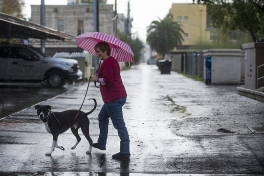 Bane the dog (left) and Mona Wolfe (right) go for a walk in the rain on Christmas morning in downtown Phoenix, Arizona on Dec. 25, 2019.