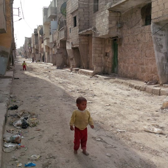 A young child walks through an alley in Aleppo, Syria, in April 2014. (Raja Abdulrahim/Los Angeles Times/TNS)