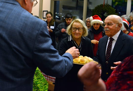 Ron and Mary Toomey distribute special Maravian buns to Christmas Eve celebrants at the Unitarian Universalist Congregation of York  to celebrate their 70th anniversary on Christmas eve, Tuesday, December 23, 2019.