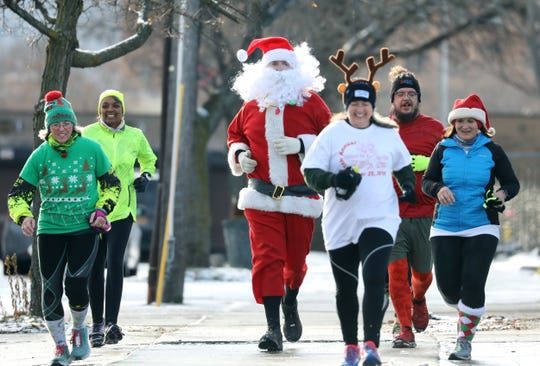 Christopher Herman of Henrietta as Santa, finishes the Annual Christmas Day Run/Walk to benefit the House of Mercy in 2018. About 40 people walked and ran Wednesday from the Culver Road Armory to the House of Mercy on Ormond Street.
