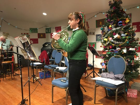 Jennifer Carmichael plays the French horn at the Christmas dinner organized by Temple Adat Elohim in Thousand Oaks Wednesday. The synagogue has organized the dinner for 25 years.