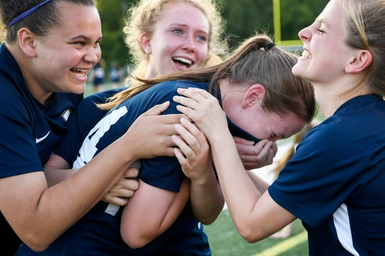 From left, Roberson's Ashley McGraw, Lucy Manner and Riley Williamson laugh as they hug Devin Simmons while she cries after the Rams tied Northern Guilford in the final minutes of the WNC regional final May 21, 2019. Roberson went on to defeat Northern Guilford 5-3 in overtime.
