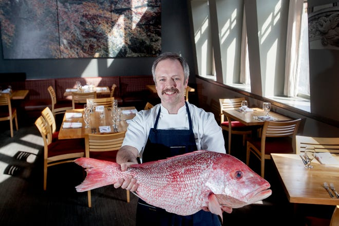 Chef William Dissen holds a red snapper at The Market Place in Asheville Feb. 21, 2019. Dissen strives to support companies that use sustainable fishing practices in his restaurant.
