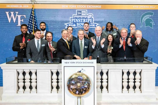 Contingents from Michigan State and Wake Forest's football teams cheer as the Spartans' Mark Dantonio and Demon Deacons' Dave Clawson ring the opening bell at the New York Stock Exchange on Thursday, Dec. 26, 2019, in New York.