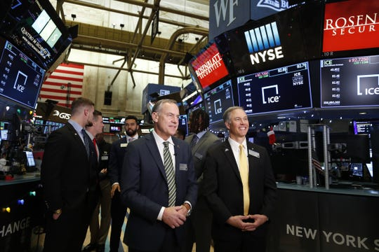Michigan State coach Mark Dantonio, let, and Wake Forest coach Dave Clawson, right, stand with their players after ringing the opening bell at the New York Stock Exchange on Thursday, Dec. 26, 2019, in New York.