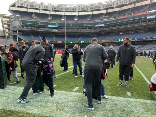 Michigan State junior offensive lineman Jordan Reid (right) helps run a drill for children from the Bronx during a football clinic Thursday, Dec. 26, 2019 at Yankee Stadium in New York for the Spartans' Pinstripe Bowl game against Wake Forest on Friday.