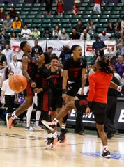 Houston players celebrate after defeating Washington 75-71 Wednesday in Honolulu.