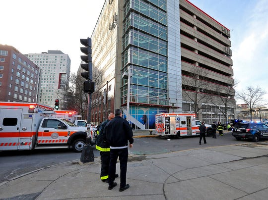 Emergency personnel at the scene of an incident at the Renaissance Park Garage where an adult and 2 children fell from the garage and were found dead on a sidewalk near the Boston parking garage on Christmas Day, Wednesday, Dec. 25, 2019.