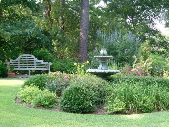 You can reduce the size of your lawn by adding a flower bed. Shrubs, perennials and a fountain are all pretty garden features, and they make this garden more attractive to birds and pollinators.