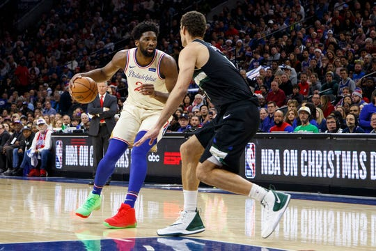 Philadelphia 76ers' Joel Embiid, left, in action against Milwaukee Bucks' Brook Lopez, right, during the first half Wednesday.