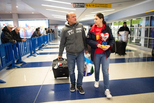 In this Tuesday, Dec. 3, 2019, photo Mohammed Hafar, left, helps his daughter Jana with her luggage as they leave JFK Airport in New York.