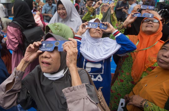 Muslim women watch a solar eclipse through special glasses at the campus of the Faculty of Astronomy of Muhammadiah University of North Sumatra (UMSU) in Medan, Indonesia, Thursday,