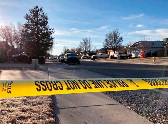 Police have a residential street cordoned off as detectives investigate the deaths of four people found Christmas Day inside a home in Rio Rancho, N.M., on Thursday, Dec. 26, 2019.  All of the victims appeared to have suffered gunshot wounds, police said in a statement posted on Facebook.