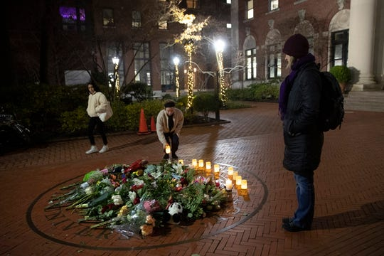 FILE - In this Thursday, Dec. 12, 2019, file photo, people pause and place a candle at a make-shift memorial for Tessa Majors inside the Barnard campus, in New York.