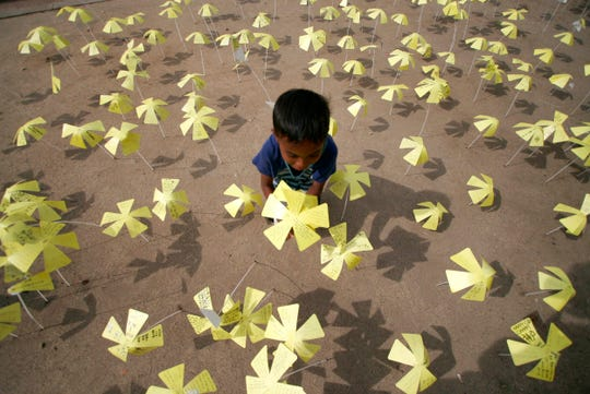An Acehnese boy plants a paper-made sakura or cherry flowers with messages of hopes written on them by Indonesian and Japanese students, during the commemoration of 6 years since 2004 Indian Ocean tsunami organized by the University of Tokyo's Earthquake Research Institute outside Baiturrahman Grand Mosque in Banda Aceh, Aceh province, Indonesia, Dec. 25, 2010.