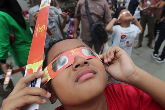 A kid looks up at the sun wearing protective glasses to watch a solar eclipse from Jakarta, Indonesia on  Thursday.