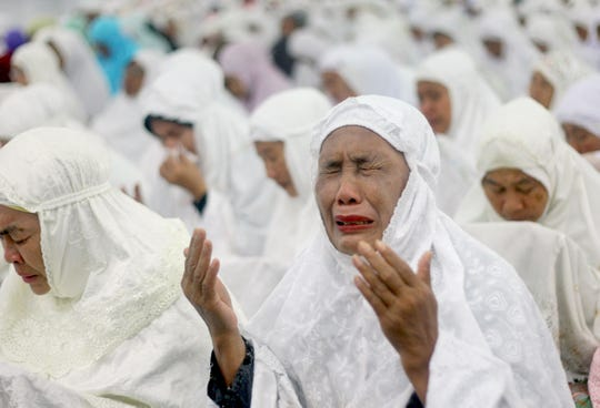 An Acehnese woman weeps during a prayer for the victims of Indian Ocean tsunami ahead of its 10th anniversary at Baiturrahman Grand Mosque in Banda Aceh, Aceh province, Indonesia, Thursday, Dec. 25, 2014.