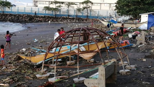Residents walks beside an outrigger and playground equipment that were damaged by Typhoon Phanfone along a coastline in Ormoc city, central Philippines on Thursday.
