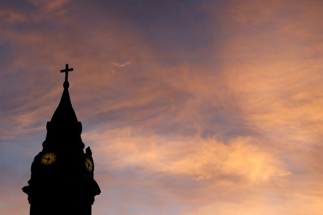 FILE - In this Sept. 27, 2015 file photo, clouds are lit by the rising sun over St. Augustine Roman Catholic Church in Philadelphia.