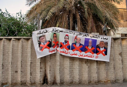 """A poster with defaced pictures of Iraqi politicians and Arabic that reads, """"the blood of the protesters and the Iraqi people is on your necks, the conspirators on the people and the religious authority,"""" in hung on the wall near Tahrir Square during anti-government demonstrations in Baghdad, Iraq, Thursday, Dec. 26, 2019."""