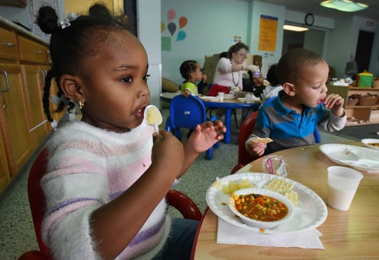 Ariyah, 3 and Nicholas, 2 enjoy a chili lunch with peaches cooked by Chef Shaune Fairley at Starfish Family Services.
