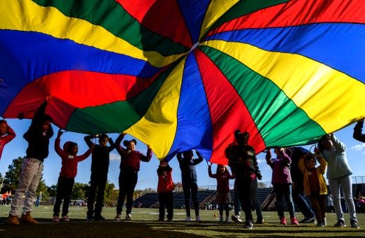 Harper Elementary School students hoist up a colorful parachute to let their classmates run underneath during a Special Education Unified Game Day at Central Stadium in Evansville, Tuesday morning, Oct. 22, 2019. The Evansville Vanderburgh School Corporation hosted Tuesday's event for more than 200 elementary school students and will host another game day for middle school students, Wednesday morning.