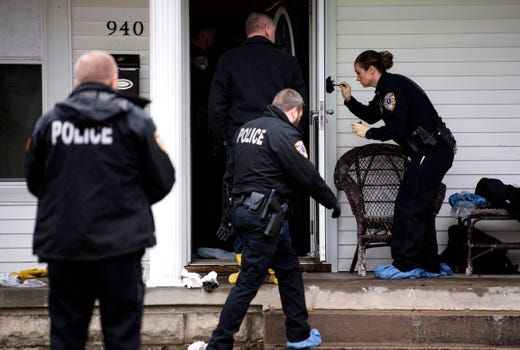 Owensboro Police Department Officer Jennifer Haynes, far right, dust for finger prints on the outside of a screen door at 940 Audubon Avenue in Owensboro, Ky., as police investigate a fatal shooting with at least four victims Thursday Jan. 17, 2019.