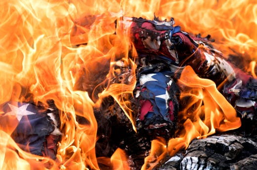Flags burn in a pile during a flag retirement ceremony at Lyles Station Historic School and Museum in Princeton, Ind. Saturday, June 15, 2019. 54 flags where retired.