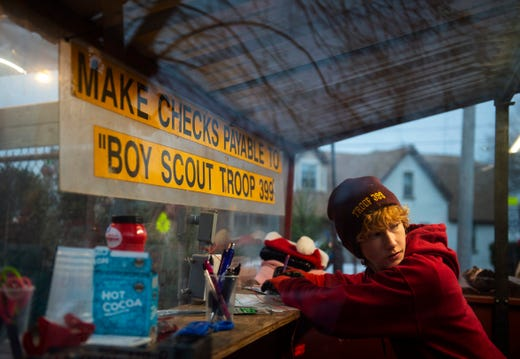 Connor McCollum, 15, of Evansville signs in to sell Christmas trees at Troop 339's annual Fundraiser, which started in 1957, at Sacred Heart Catholic Church in Evansville, Monday afternoon.
