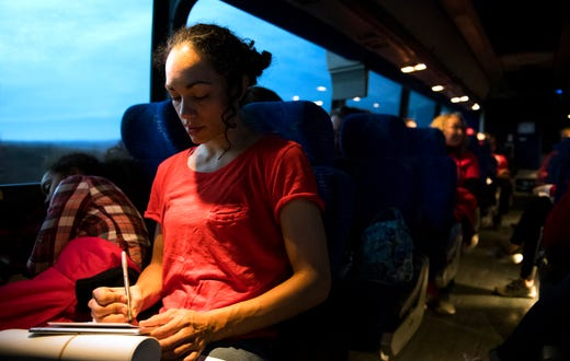 Reitz High School art teacher Sadia Brimm, right, writes a letter to state representatives while her daughter, Jada Ragland, 11, sleeps on the bus ride to the Indiana Statehouse to participate in Red for Ed Action Day in Indianapolis, Ind., Tuesday morning, Nov. 19, 2019.