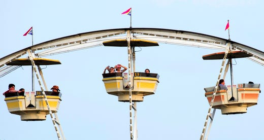 Riders take in the view and snap photos at the top of the Ferris wheel during the 98th Annual West Side Nut Club Fall Festival Thursday evening, Oct. 10, 2019.