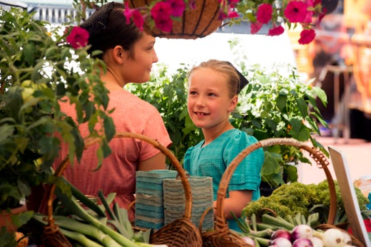 Janae Stoll, left, glances at Megan Stoll, right, while selling produce and flowers at the seasons first Market on Main Wednesday, June 5, 2019. Market on Main is held every Wednesday in front of the Ford Center through September 18.