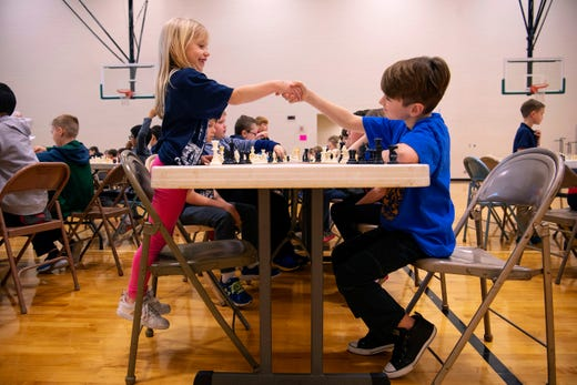Lillly Happe, 7, Oak Hill Elementary School, left, is congratulated on her win by Ellis Murphy, 9, Scott Elementary School during the K-12 Spring Scholastic Chess Tournament at North Junior High School Saturday.