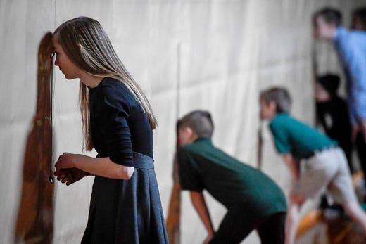 Waiting backstage, Hayden Tichenor, 14 years-old, watches action on the stage, with other performers, through holes in the curtain during the Catholic Schools Week Talent Show at Henderson's Holy Name School Wednesday, February 6, 2019.