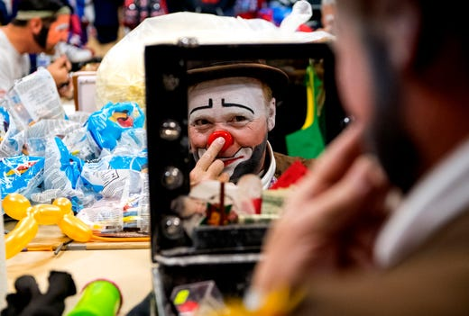 """Hadi Funsters guest clown Mike """"Squeeky"""" Kapshandy of Springfield, Ill., applies pressure to secure his clown nose while he prepares for the 86th Hadi Shrine Circus at Ford Center Friday morning, Nov. 29, 2019."""