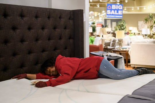 Tamisha Dilworth tests out the comfort of a mattress as she shops for furniture at Ashley HomeStore in Evansville, Friday afternoon, March 1, 2019. While working for her Habitat house and sleeping on the couch or the floor at her father's house, she frequently dreamt about how good it would feel to have her own bed again.