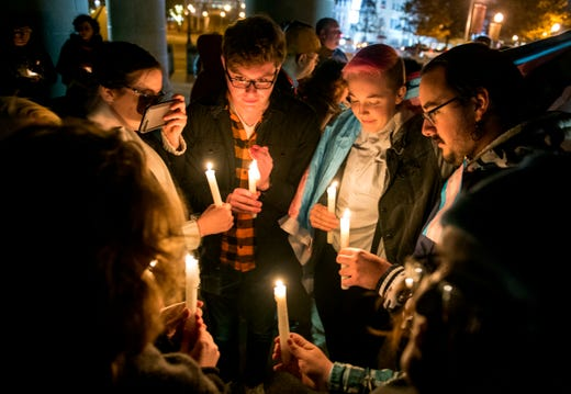 People gather in a moment of silence at the Four Freedoms Monument during the Queer Space Transgender Day of Remembrance vigil in Downtown Evansville, Ind., Wednesday evening, Nov. 20, 2019.