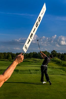 """Volunteer Martha Hardesty of Owensboro, Ky., holds up a sign that says """"quiet please"""" as Whee Kim of South Korea tees off on Hole 1 during the first round of the Korn Ferry Tour Championship at Victoria National Golf Club in Newburgh, Ind., Friday, Aug. 30, 2019. The golf tournament will continue through Labor Day, Monday, Sept. 2."""